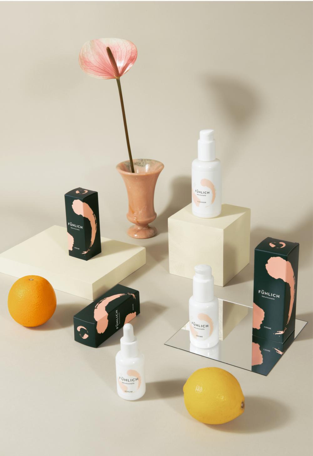 Das FÜHLICH Naturkosmetik Trio in einem Setting mit Zitrone, Orange und einer Rosinen Blume