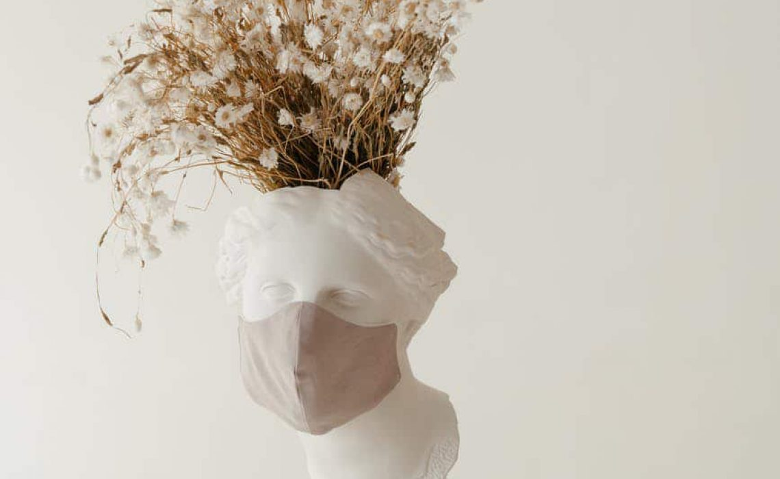 Eine weiße Skulptur mit einem Mund Nasen Schutz und Trockenblumen als Haare